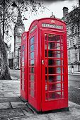 stock photo of british culture  - A pair of traditional red phone booths in London with the Big Ben in a desaturated background - JPG
