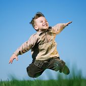 Happy little boy jumping in field against blue sky