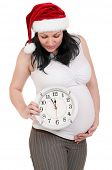 Portrait of a pregnant woman in santa hat with clock over white background. Third trimester. poster