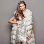 Fashion Portrait Young Woman In White Fur Coat. Girl With Elegant Hairstyle Posing On A Gray Backgro poster