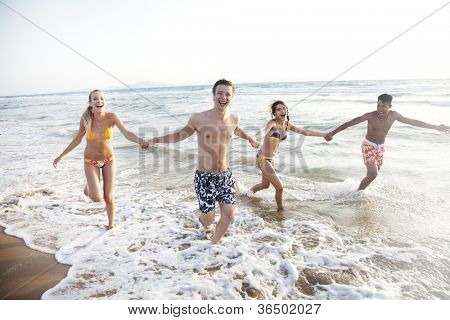 group of young people having fun, running in the surf