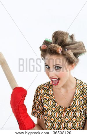 Portrait of pretty young woman with hair curlers screaming out while holding rolling pin over white background