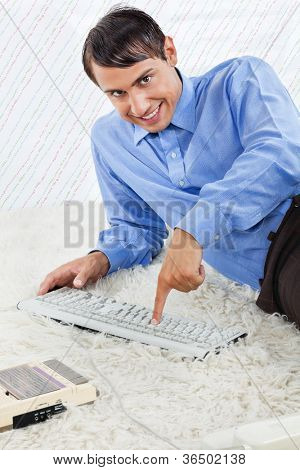 Portrait of geek businessman pressing keyboard keys while lying down on rug with an old fashioned cassette player