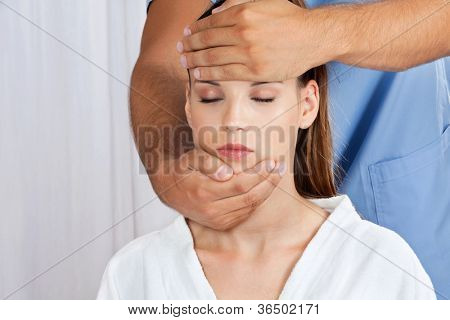 Male masseuse giving a head massage to woman at health spa
