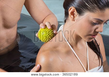 Young mixed race woman receiving back massage with stress ball by male therapist