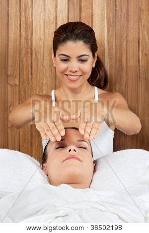 Young woman receiving massage from a female masseur at health spa