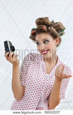 Beautiful young woman with hair curlers taking self portrait photograph through camera