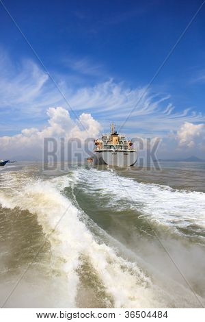 Boat wake and cargo ship to the sea