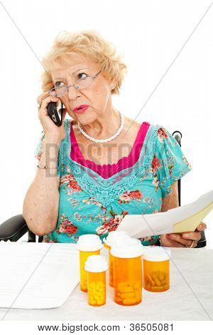 Senior woman on the phone discussing her medical bills with the health insurance company.  White background.