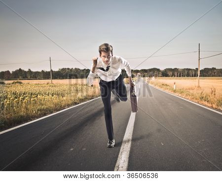 Young businessman running fast on a countryside road