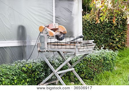 A tile saw on the lawn of a home that is being remodeled.  The window is covered with plastic sheeting to protect it from the over spray.