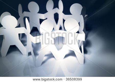 Team of paper doll people holding hands in a circle