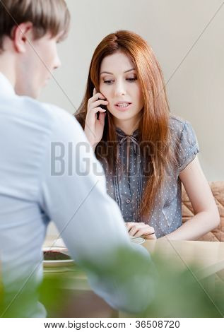 Woman speaks on the phone sitting with boyfriend at the cafe