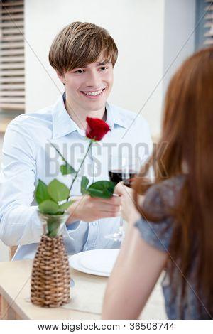 Par é no restaurante sentado à mesa com o vaso e a rosa escarlate nele