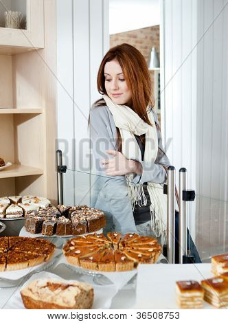 Woman in scarf looking at the bakery showcase full of different pieces of tarts