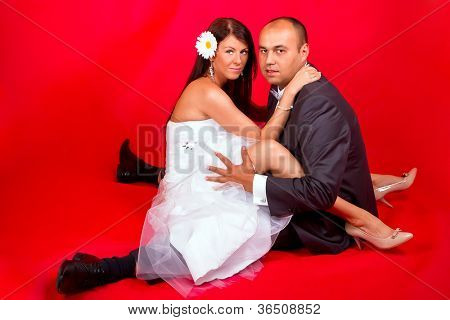 Bride and groom posing over red background