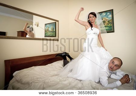 Bride and groom having fun on hotel bed