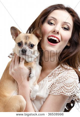 Pretty volunteer keeps on the hands a straw-colored small dog from pet asylum, isolated on white