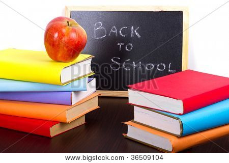 Back to school sign on a blackboard with books and apple in front