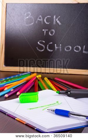 Back to school sign on a blackboard with books and pencils