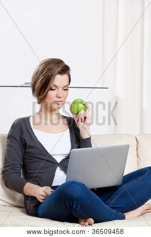 Sitting on the white leather sofa beautiful woman eats a green apple