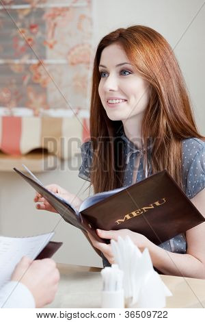 Woman keeps the menu choosing a dish to make an order