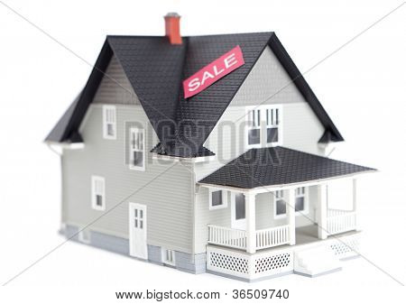 Real estate concept - home architectural model with sale sign, isolated