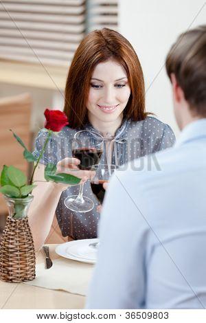 Par é da casa de café sentado à mesa com o vaso e a rosa escarlate nele