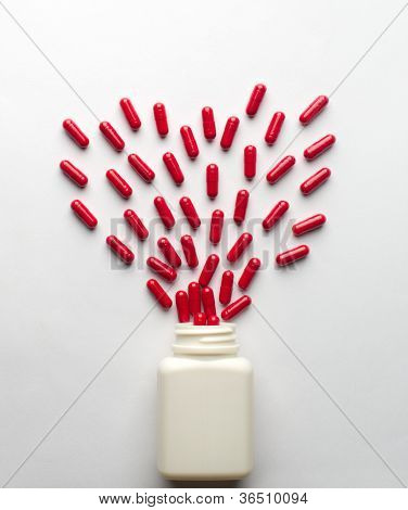 Pills spilling from an open bottle in heart symbol