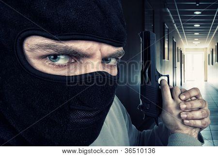 Close-up of serious armed criminal with gun