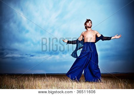 Fashionable male model posing in the field over stormy evening sky.