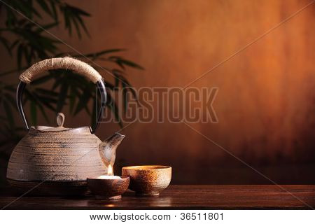 Black iron asian teapot and burning candle,vintage style.