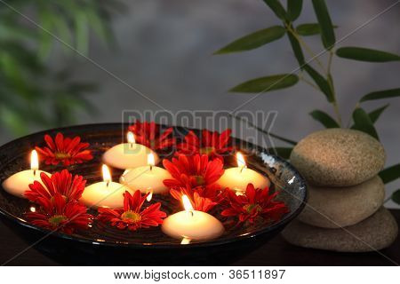Aromatic candles and red daisy in bowl,zen concept.