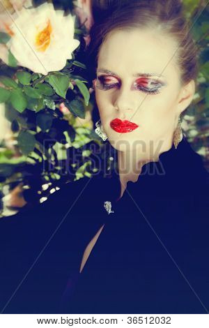 beautiful woman with grunge dramatic makeup outside wearing vintage velvet cape and expensive jewelry