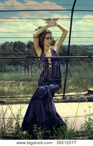 beautiful woman in long blue dress posing outside in summer hot sun in grunge setting with vintage artistic effect