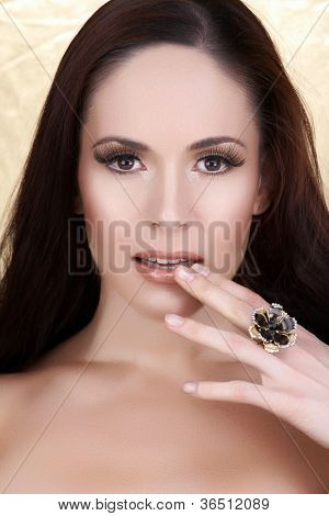 beautiful woman with long brown hair wearing natural make-up and long false eyelashes touching lips with her hand