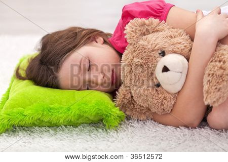 Young girl taking a peaceful nap with her favorite teddy bear