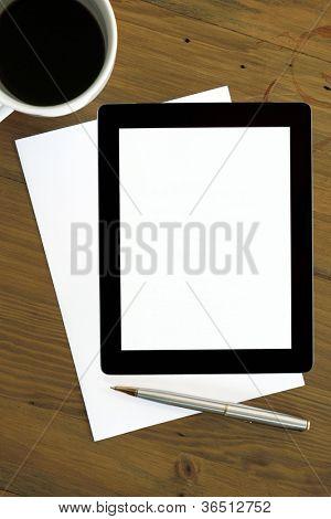 Tableta digital con pantalla en blanco, sobre el papel en blanco, con taza de café y lápiz.  Listo para su mensaje