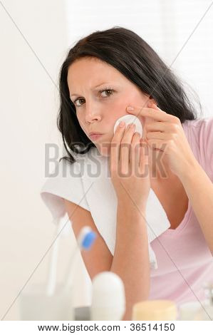 Young brunette woman in bathroom squeezing pimple cleaning acne skin