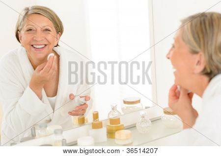 Senior woman smiling cleaning face make-up removal bathroom mirror reflection