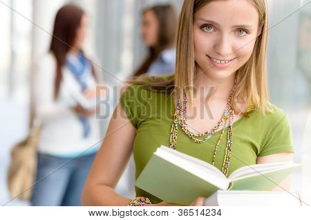 Female student reading book at high school library hall