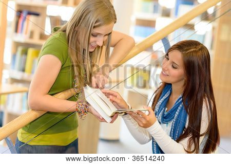 Two young student girls on high school library stairs