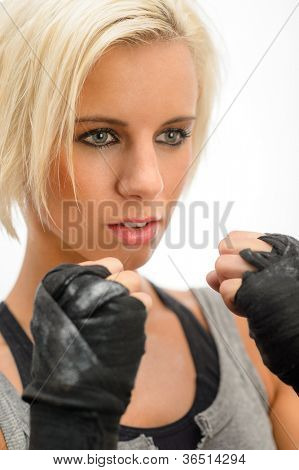 Blond rough woman ready to fight with boxing bandage gloves