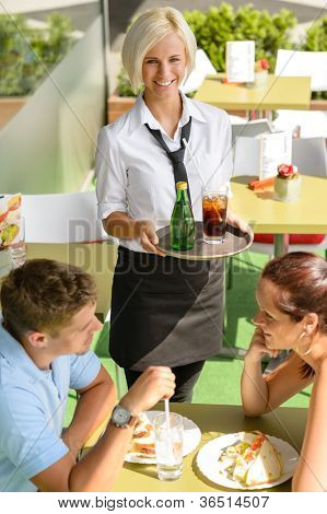 Waitress bringing beverages on tray couple cafe terrace woman man
