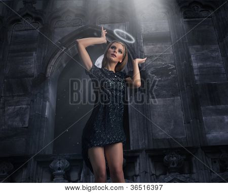 Sexy young beauty as a black angel