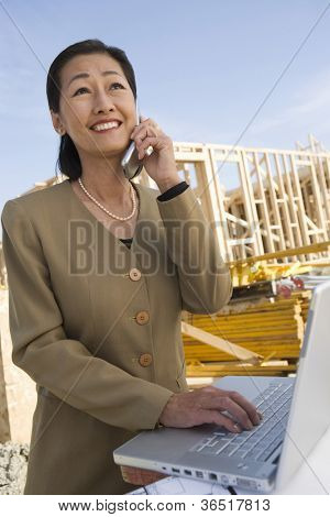 Architect with laptop using cell phone at construction site