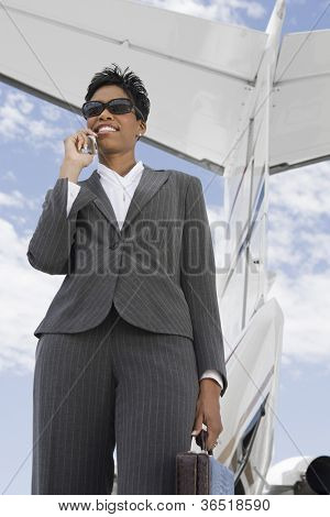 Low angle view of businesswoman using cell phone against wing tail of airplane at airfield