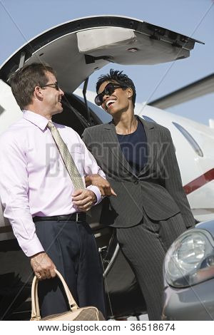 Low angle view of multi ethnic business couple standing together by airplane at airfield