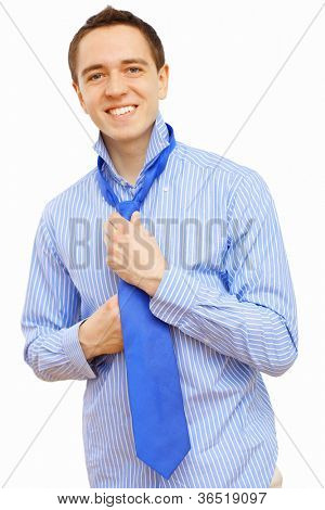 Young businessman at home preparing for a work and making his tie