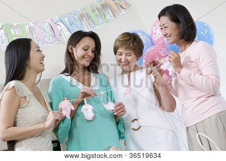 Glückliche schwangere Frau mit Freunden halten künstliche Babykleidung auf Baby-Dusche